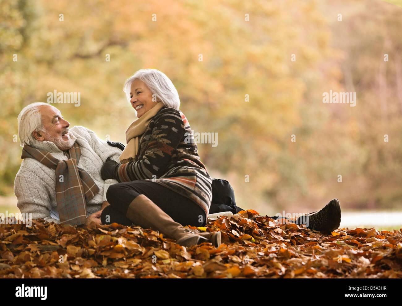 Coppia di anziani seduti in foglie di autunno Immagini Stock