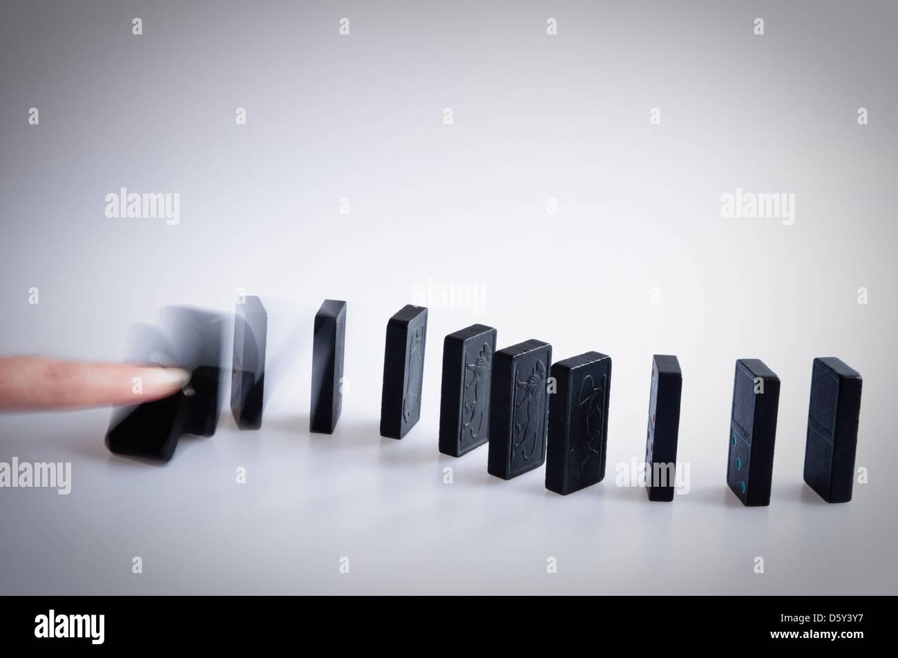 La caduta del domino - dito spingendo oltre il primo domino e mostrando il motion blur che cade. Immagini Stock