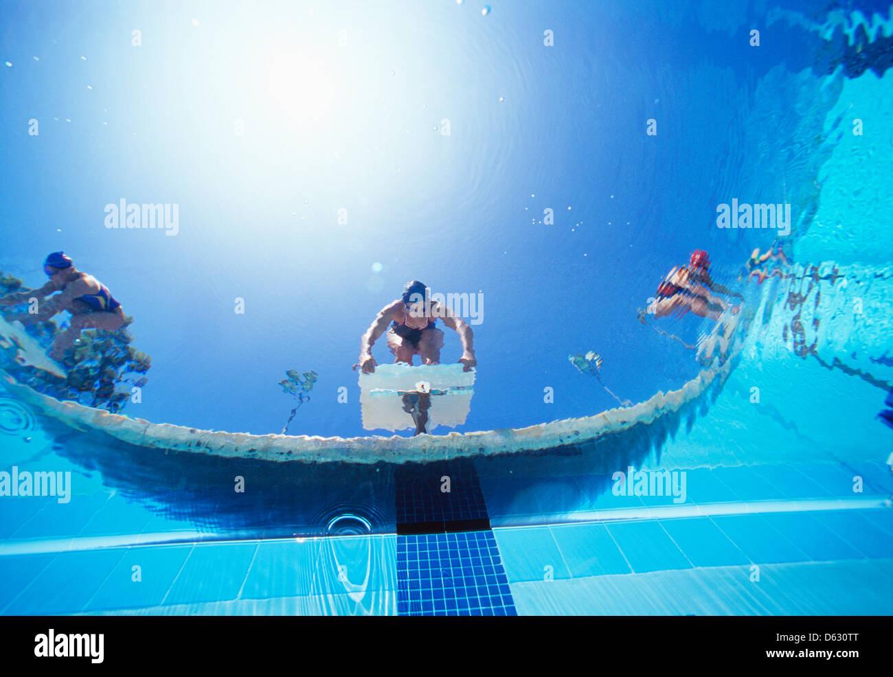 Bassa ngle vista di nuotatori femmina pronto tuffo in piscina dalla posizione di partenza Immagini Stock