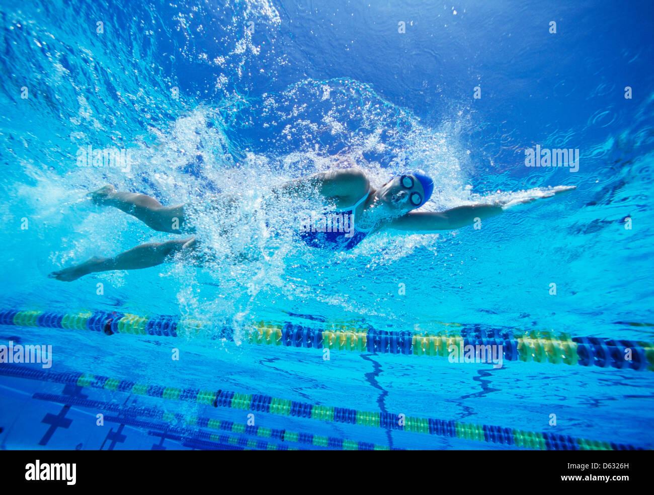 Nuotatore femminile negli Stati Uniti il costume da bagno durante il nuoto in piscina Immagini Stock