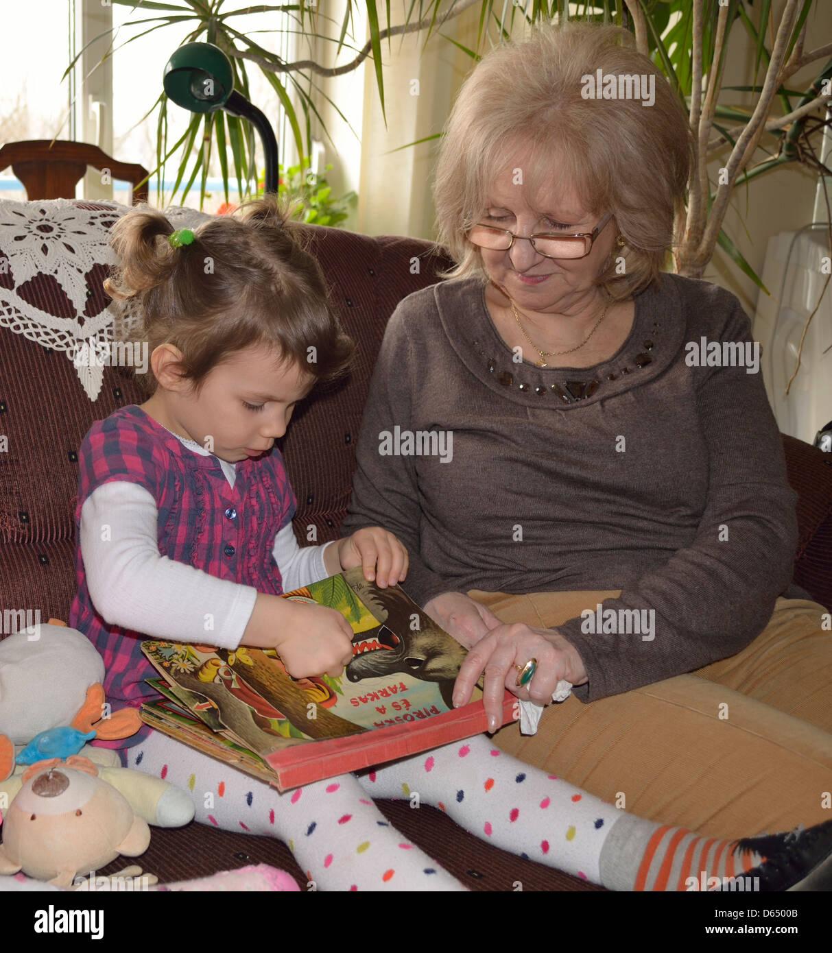 Bambina la lettura di Cappuccetto Rosso con la nonna Immagini Stock 508274ee1b