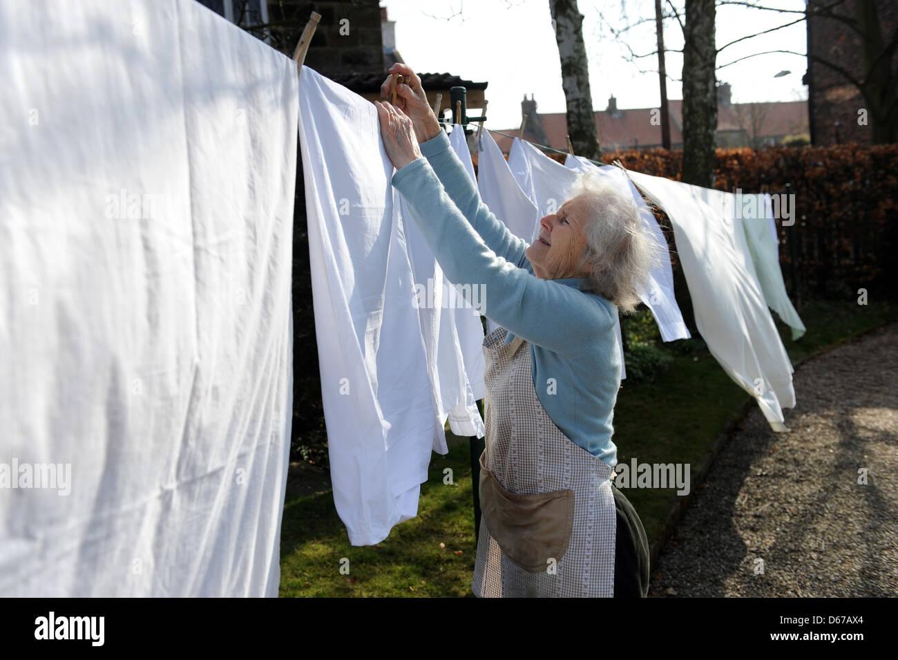 Anziano pensionato appendere fuori una linea di lavaggio sulla sua linea di lavaggio in aprile. Immagini Stock