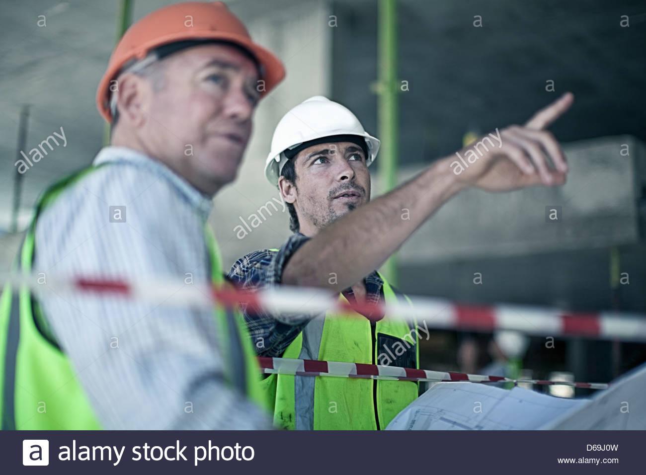 Lavoratori edili utilizzando blueprint Immagini Stock
