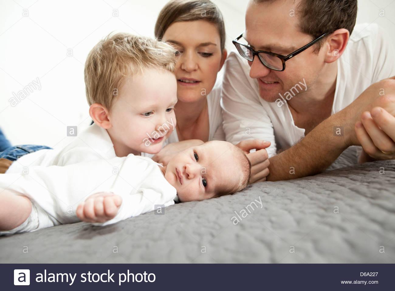 Famiglia insieme di posa su letto Immagini Stock