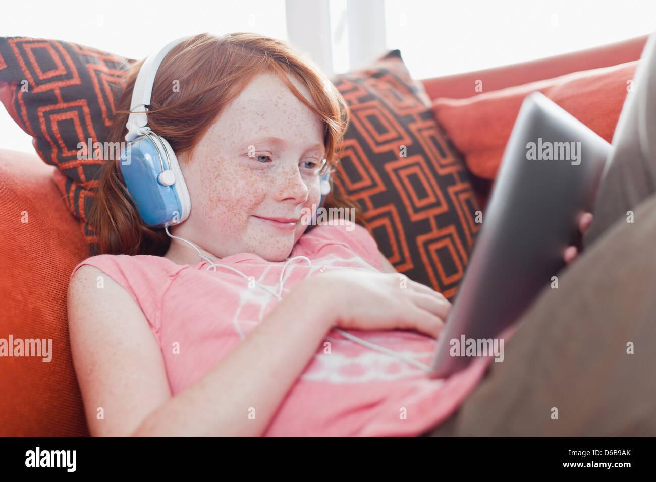 La ragazza di cuffie utilizzando computer tablet Immagini Stock
