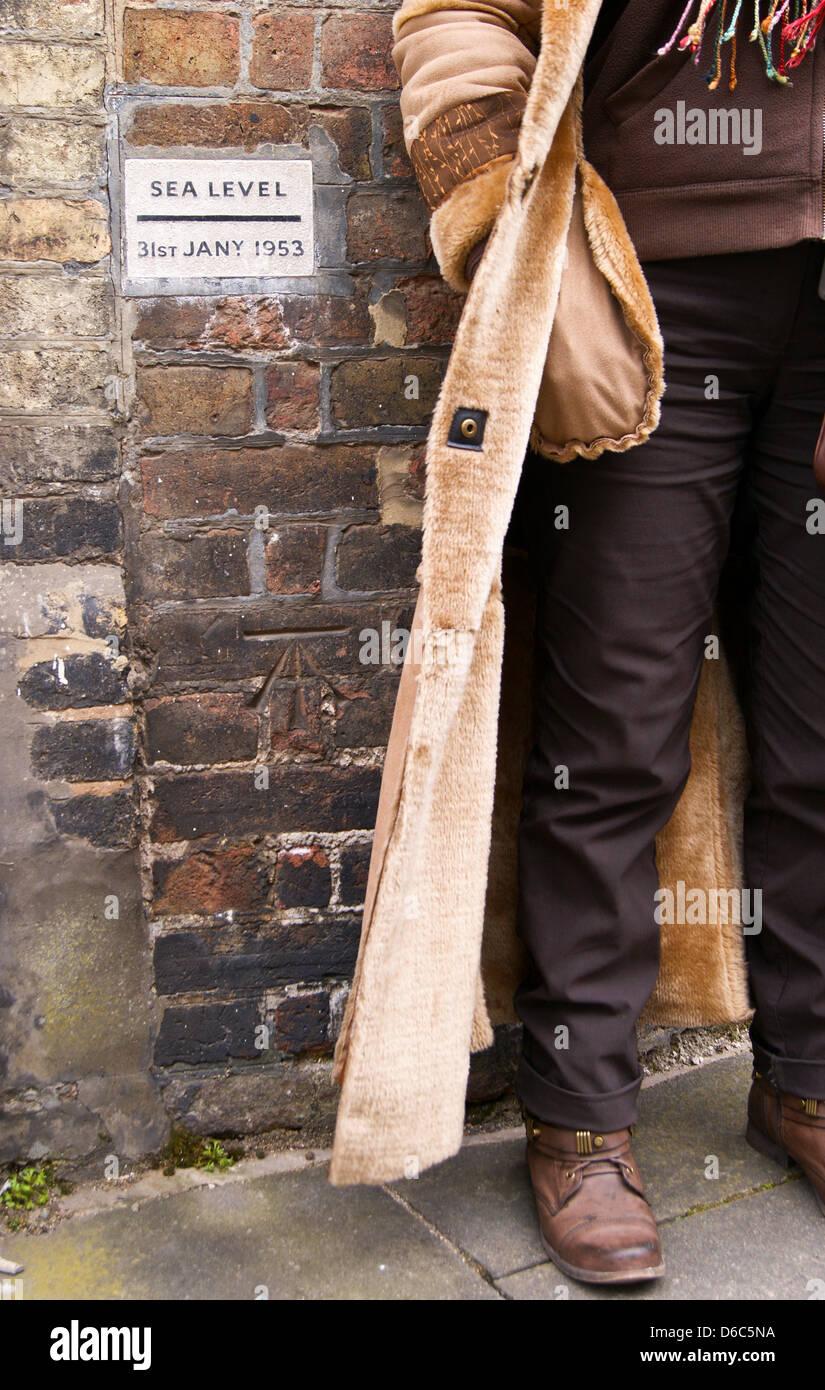 Una donna in stivali e una lunga pelliccia in piedi accanto