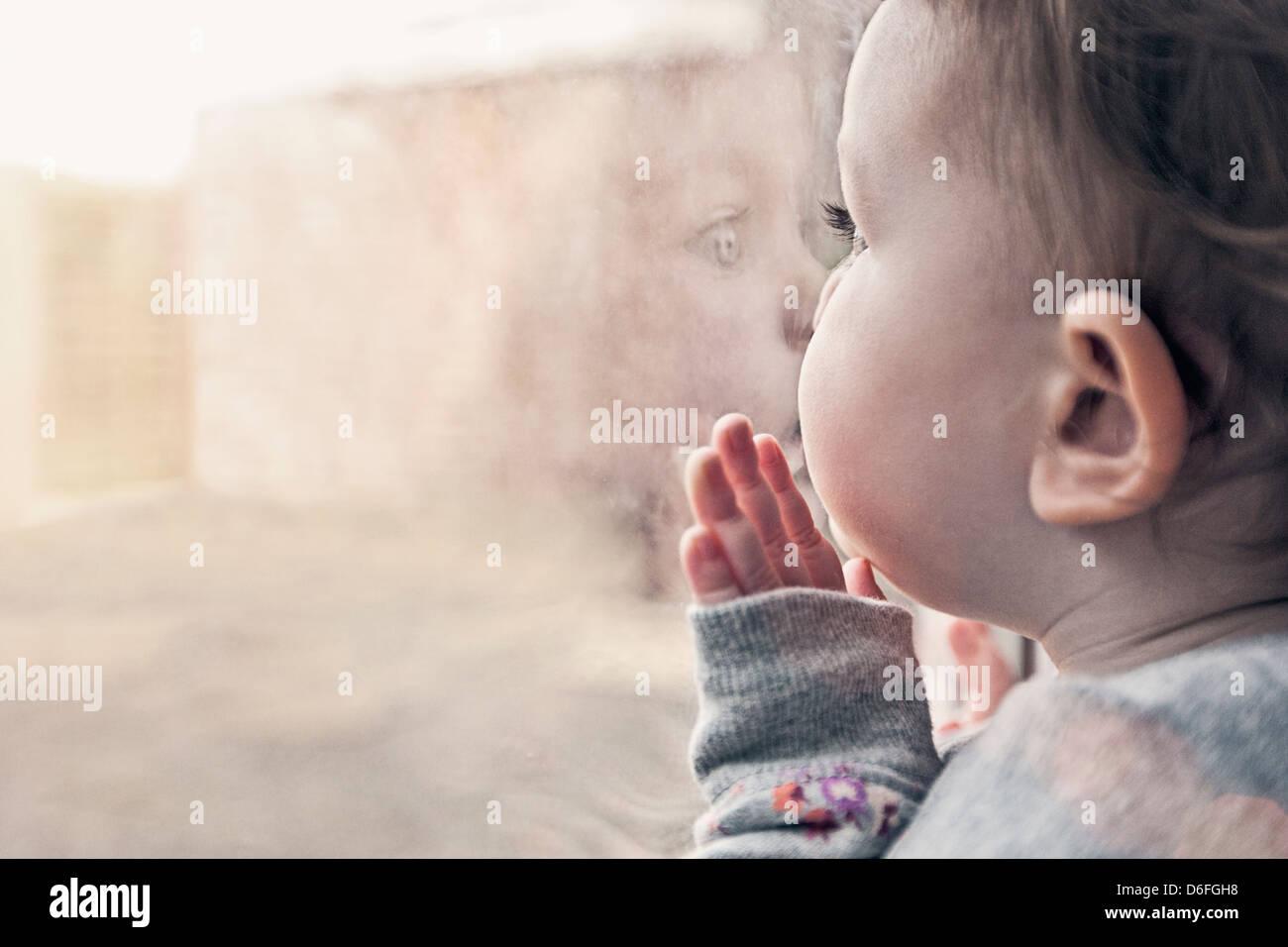 Carina ragazza infantile a guardare fuori dalla finestra Immagini Stock