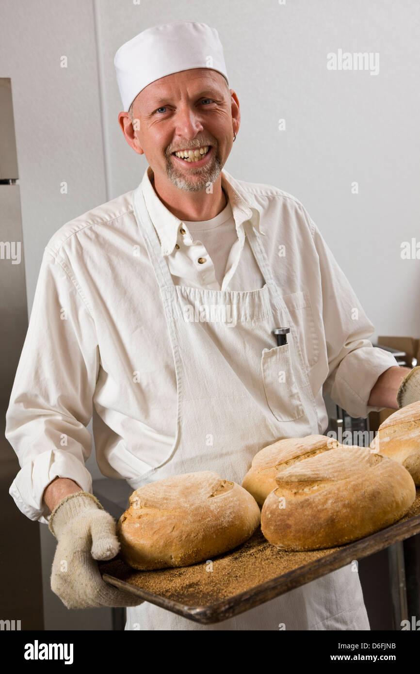 Cuoco professionista, preparare il pane fresco in un forno commerciale Foto Stock