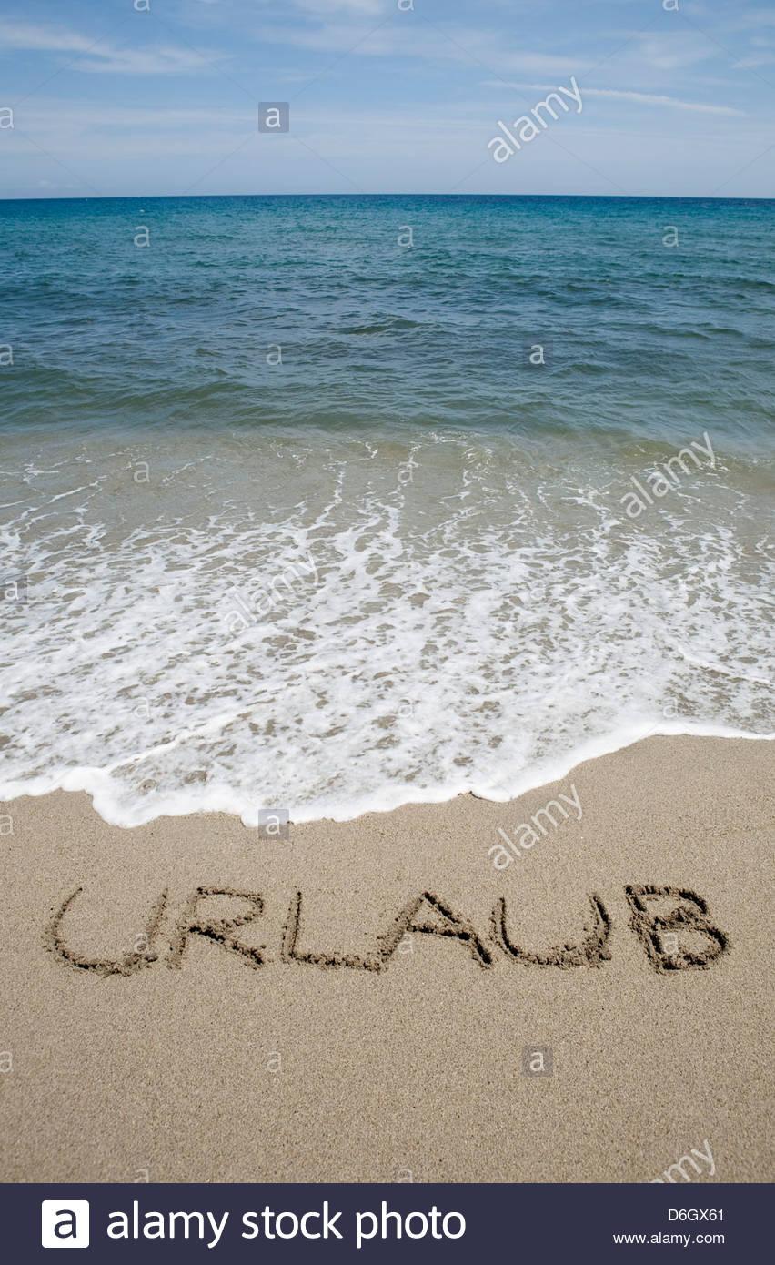 Parola tedesca per le vacanze scritto in sabbia Prunete Corsica Immagini Stock