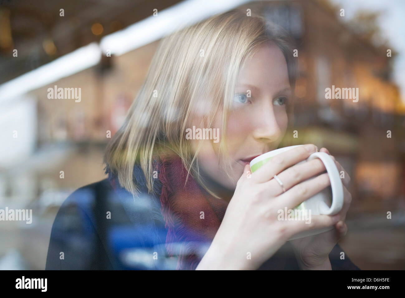 Donna di bere tazza di caffè nella caffetteria Immagini Stock