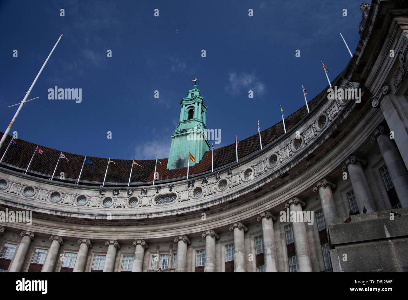 Londra Inghilterra County Hall serrati shot con numerose bandiere e un luminoso cielo blu. Immagini Stock