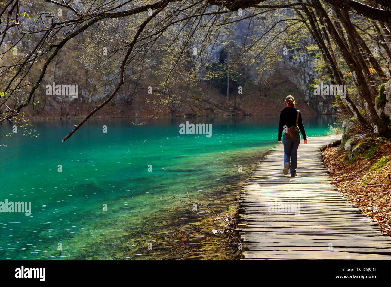 Visitatore sul marciapiede percorso su acque cristalline del Parco Nazionale dei Laghi di Plitvice, patrimonio mondiale Immagini Stock