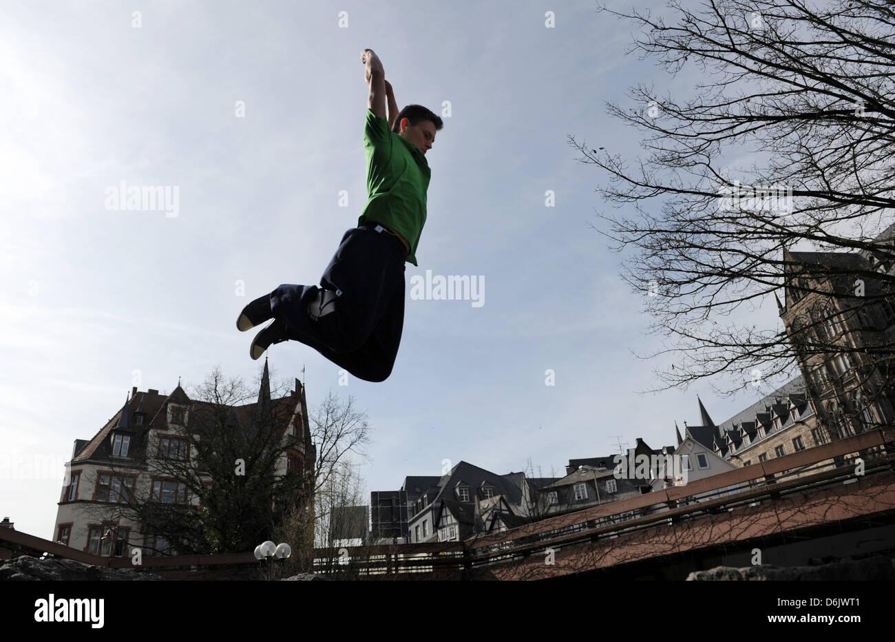 Marko salta sopra la fontana sul Rudolphsplatz in Marburg, Germania, 27 marzo 2012. Il parkour è uno sport Immagini Stock