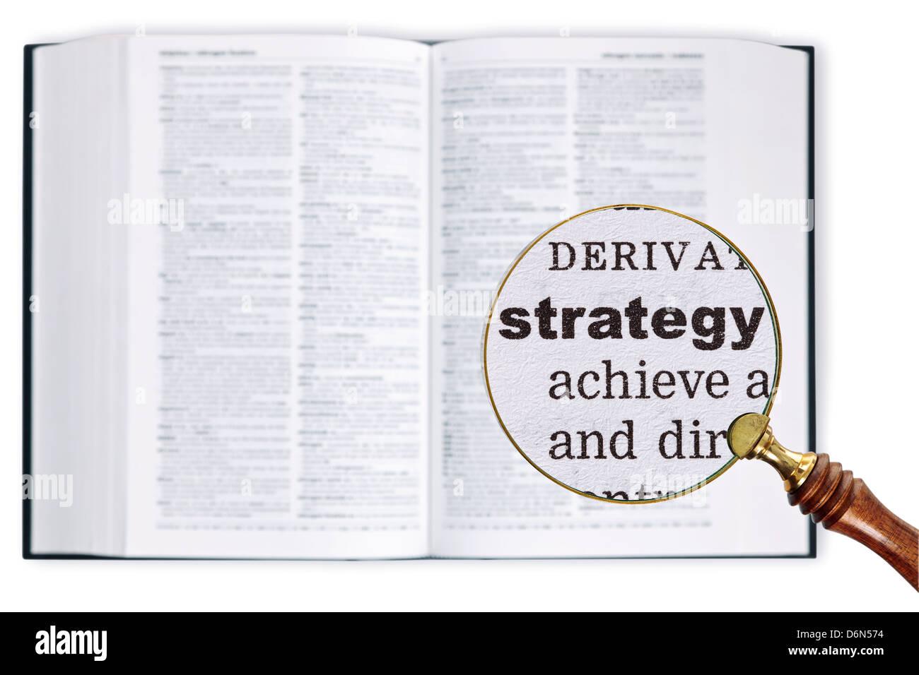 Una lente di ingrandimento detenute nel corso di un dizionario guardando la strategia di parola in scala ingrandita Immagini Stock