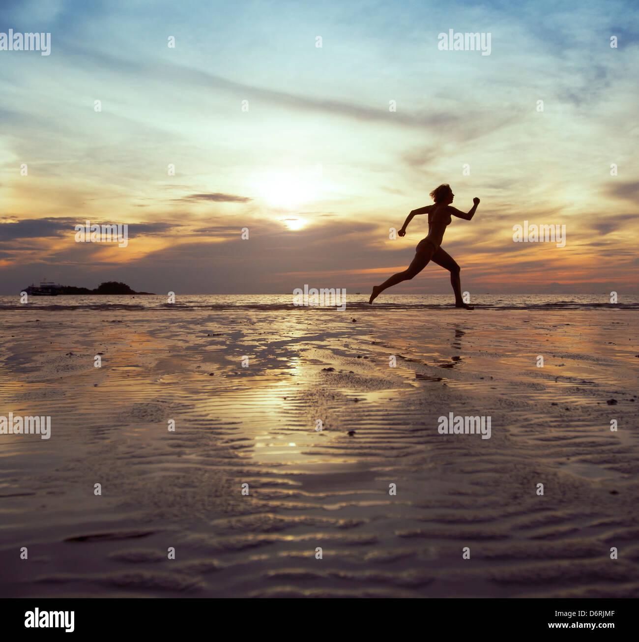 Obiettivo, silhouette di donna a piedi nudi in esecuzione sulla spiaggia Immagini Stock