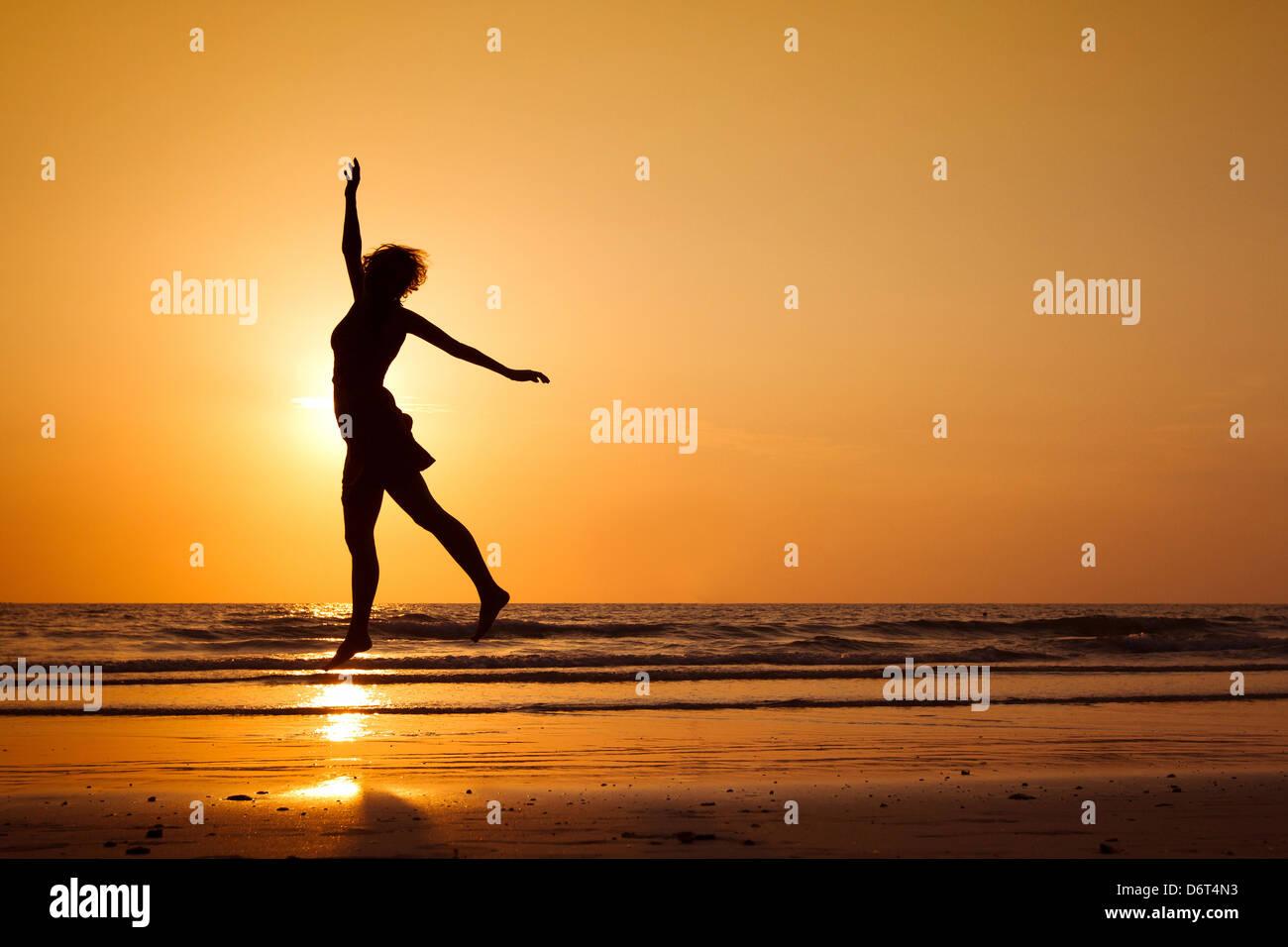 Silhouette di donna felice salto sulla spiaggia, uno stile di vita sano Immagini Stock
