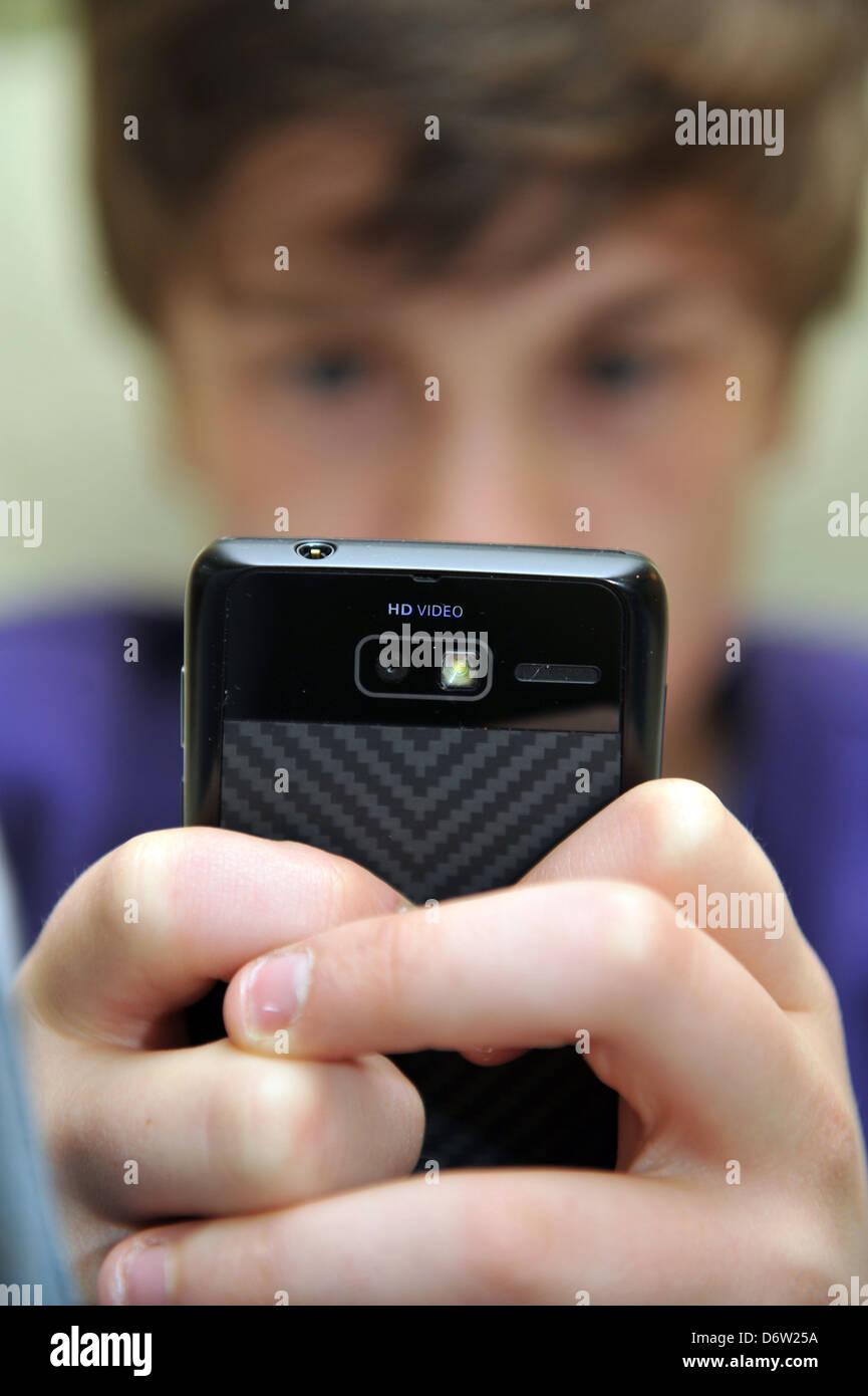 Ragazzo di dodici anni utilizza il suo telefono mobile per il social networking modello rilasciato Immagini Stock
