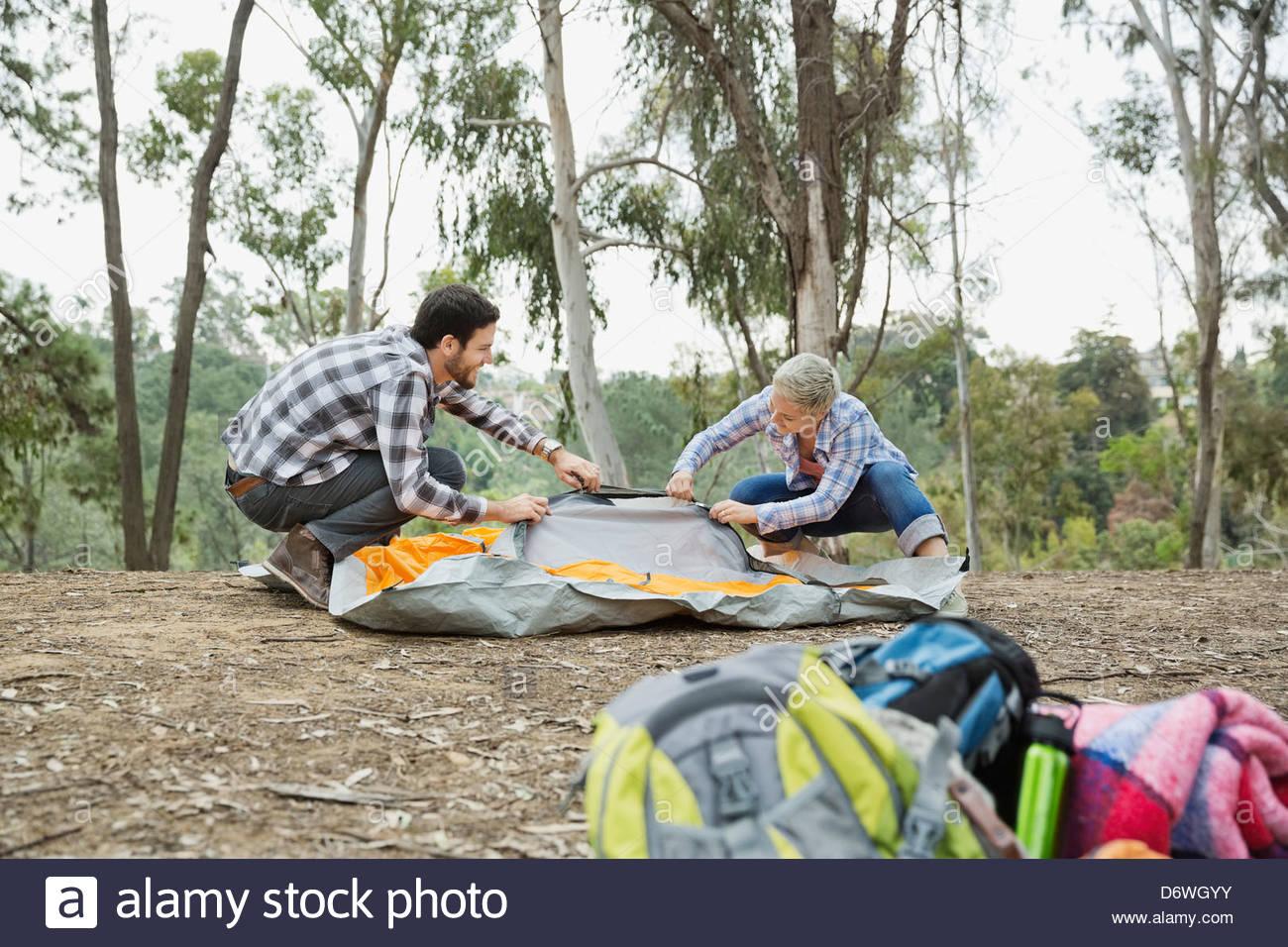 Paio di impostazione di tenda in foresta con zaini in primo piano Immagini Stock