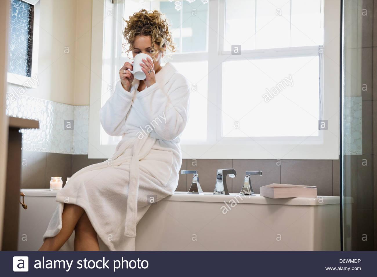 Donna matura in accappatoio di bere il caffè seduti sulla vasca da bagno Immagini Stock