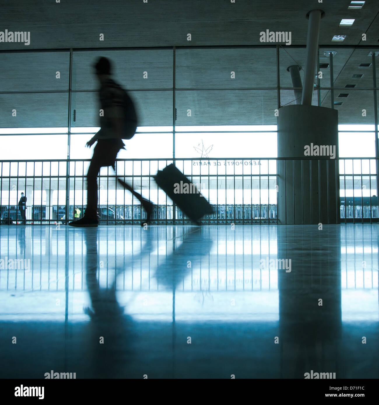 Aeroporto di astratto e silhouette di persona a piedi con i bagagli Immagini Stock