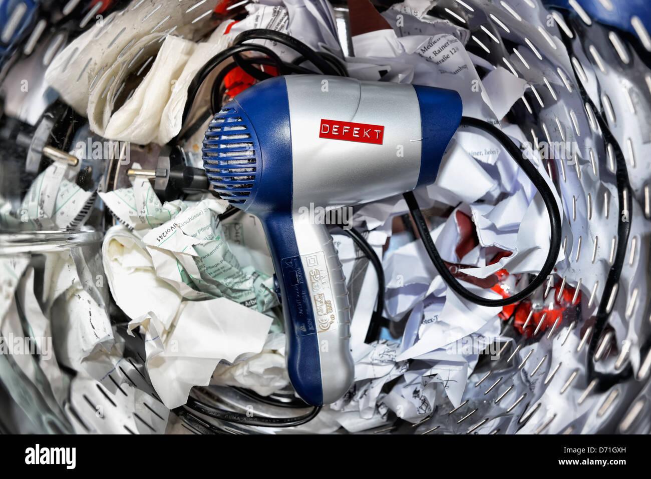 Asciugacapelli difettoso nel cestino della carta straccia, simbolico foto indossando le parti in apparecchi elettrici Immagini Stock