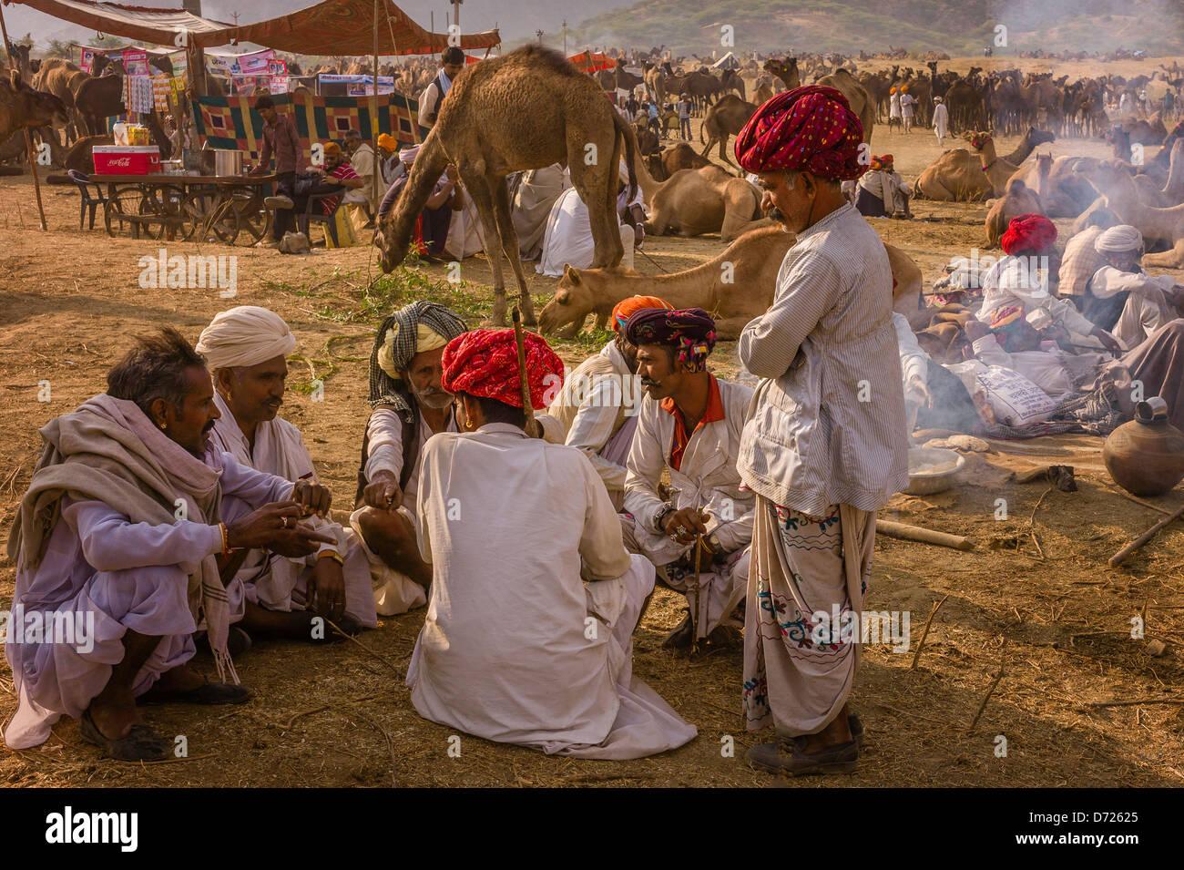 Rajput di commercianti discutere le operazioni di acquisto e di vendita di cammelli presso la fiera annuale a Pushkar, Immagini Stock