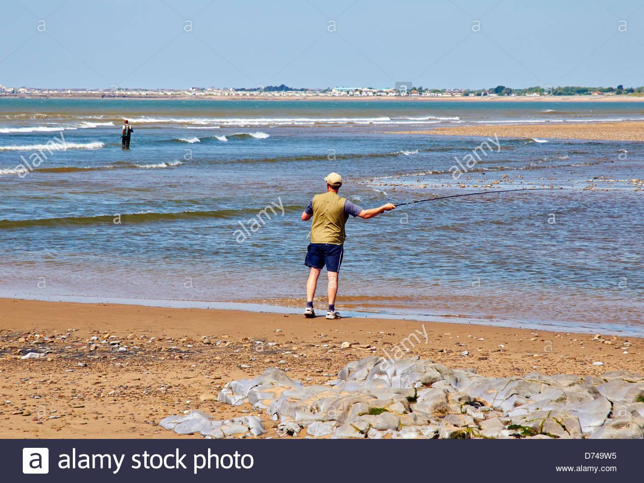 Mare il pescatore con canna da pesca polo sulla spiaggia lungo la costa  della linea di colata in acqua per catturare i pesci in piedi sulla sabbia 2e5ace1b4d01