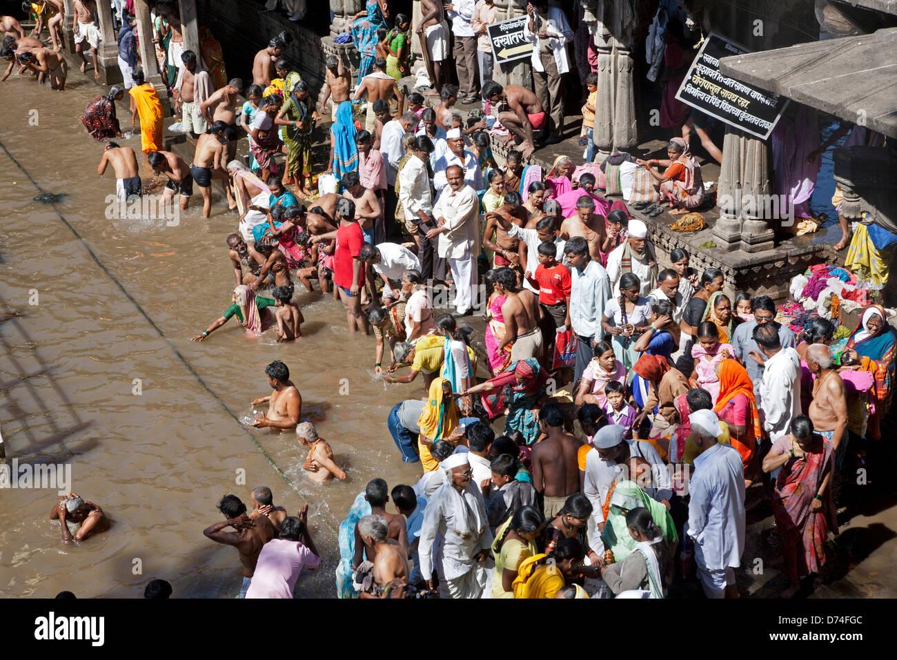 Pellegrini indù la balneazione in acqua sacra serbatoio di Kushavarta (la sorgente del fiume Godavari). Trimbakeshwar. Immagini Stock
