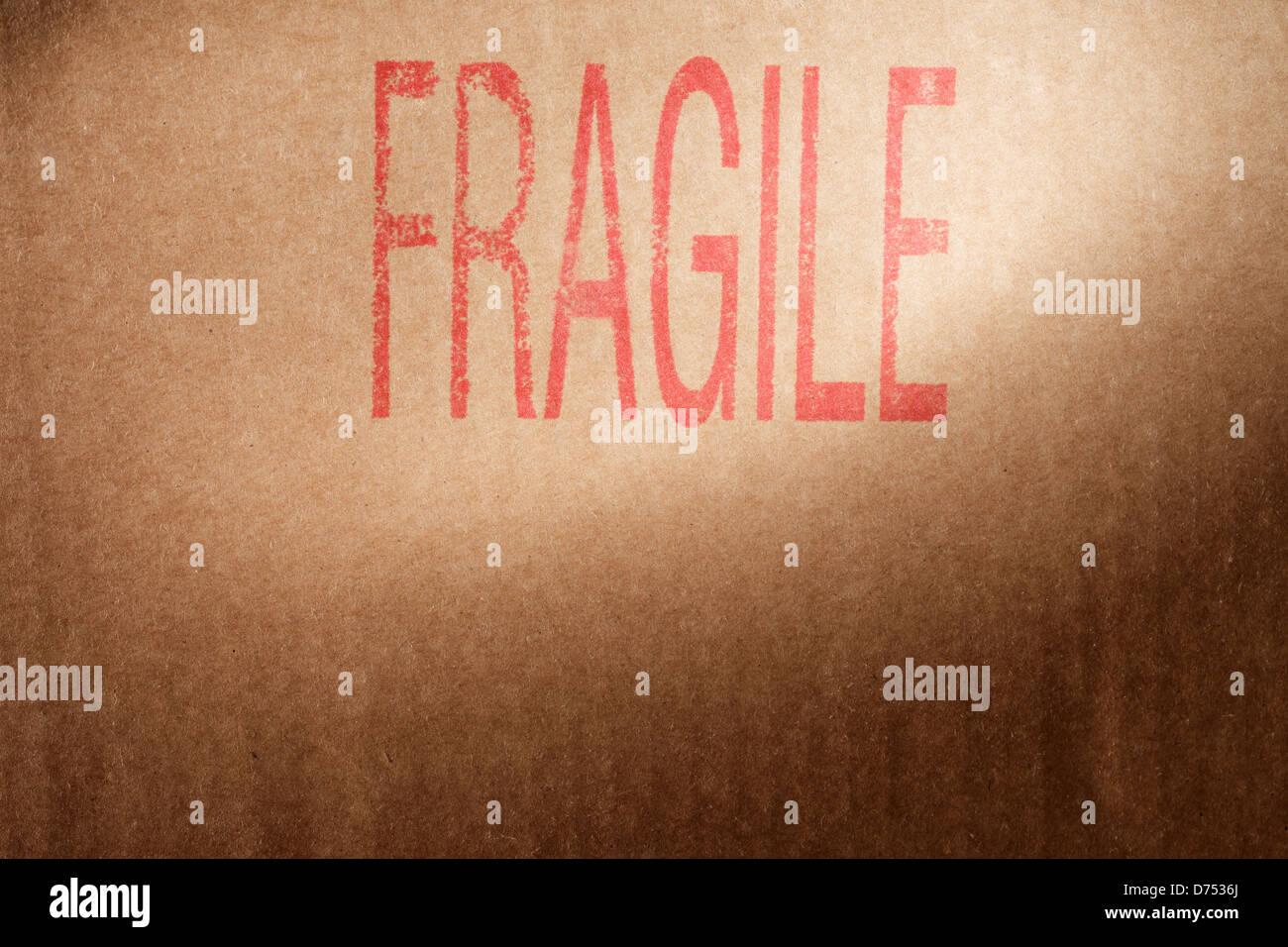 Primo piano di un marrone scatola di cartone con la parola 'Fragile' stampata con inchiostro rosso. Immagini Stock