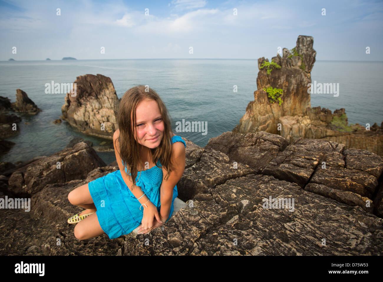 Teengirl in un vestito blu nelle rocce della costa in Thailandia. Immagini Stock