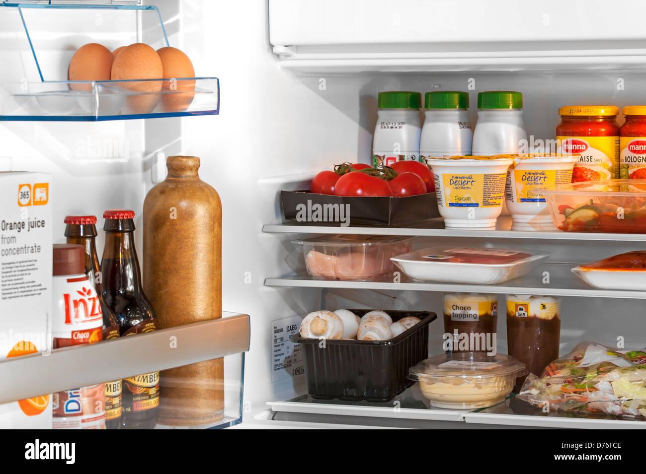 Si raffredda il cibo e le bevande in frigo aperta / frigorifero in cucina Immagini Stock