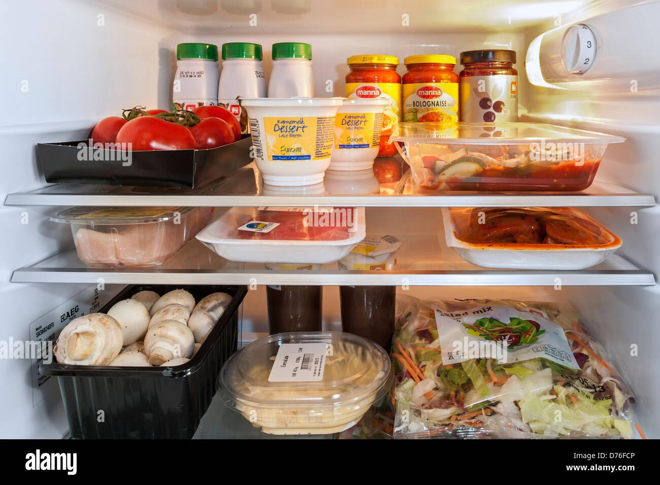 Si raffredda il cibo in frigo aperta / frigorifero in cucina Immagini Stock