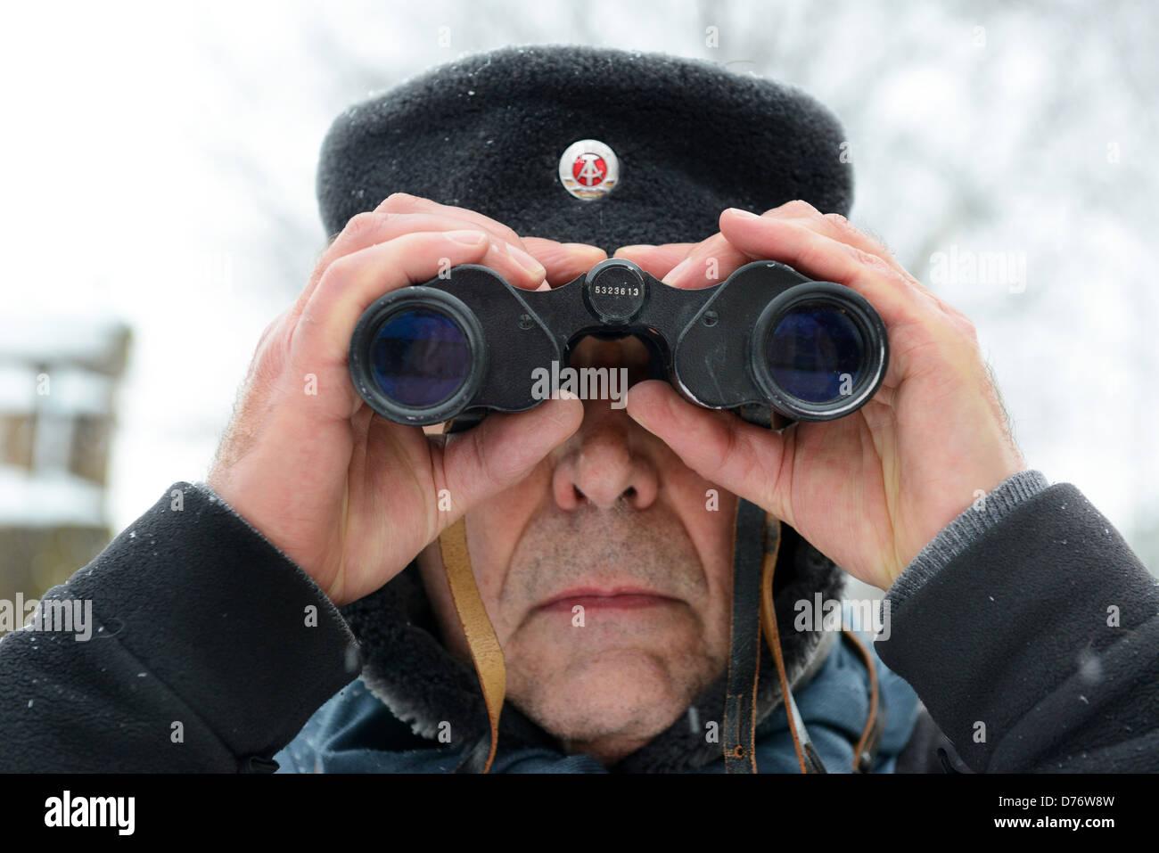 Uomo che guarda attraverso il binocolo indossando il vecchio confine tedesco-orientale guard hat Immagini Stock