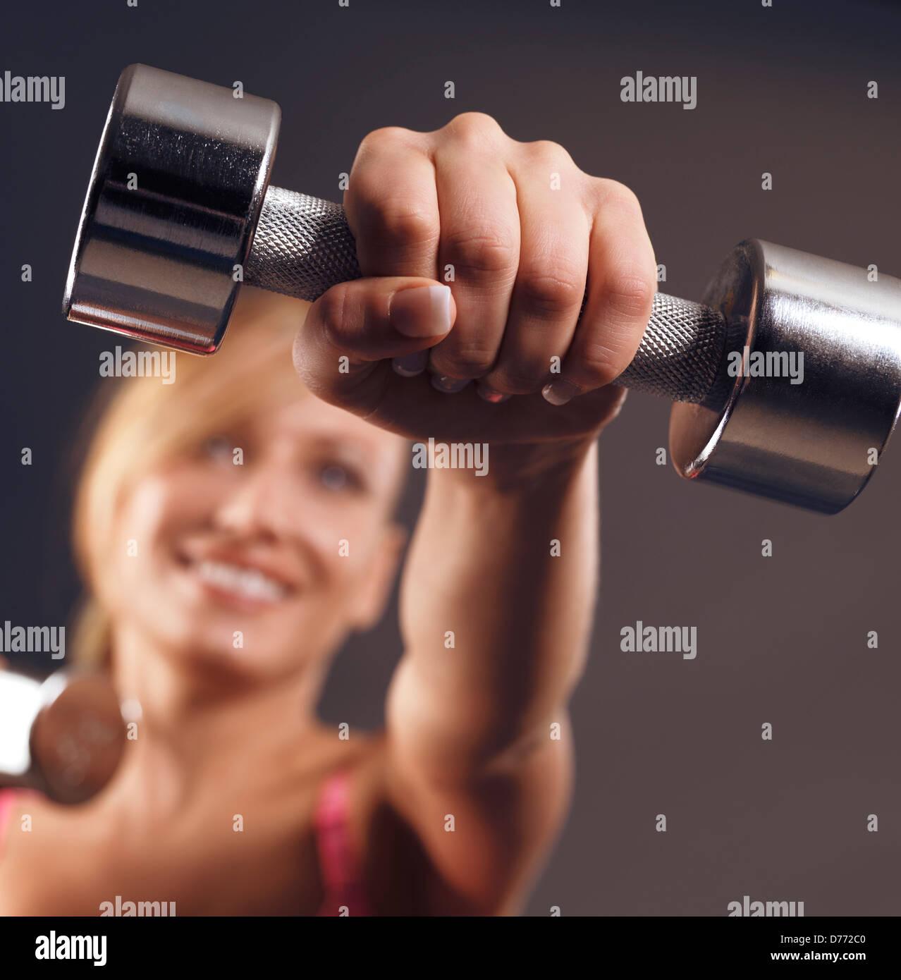 Giovane donna sorridente facendo cardio fitness con pesi, primo piano di una mano con un manubrio Immagini Stock