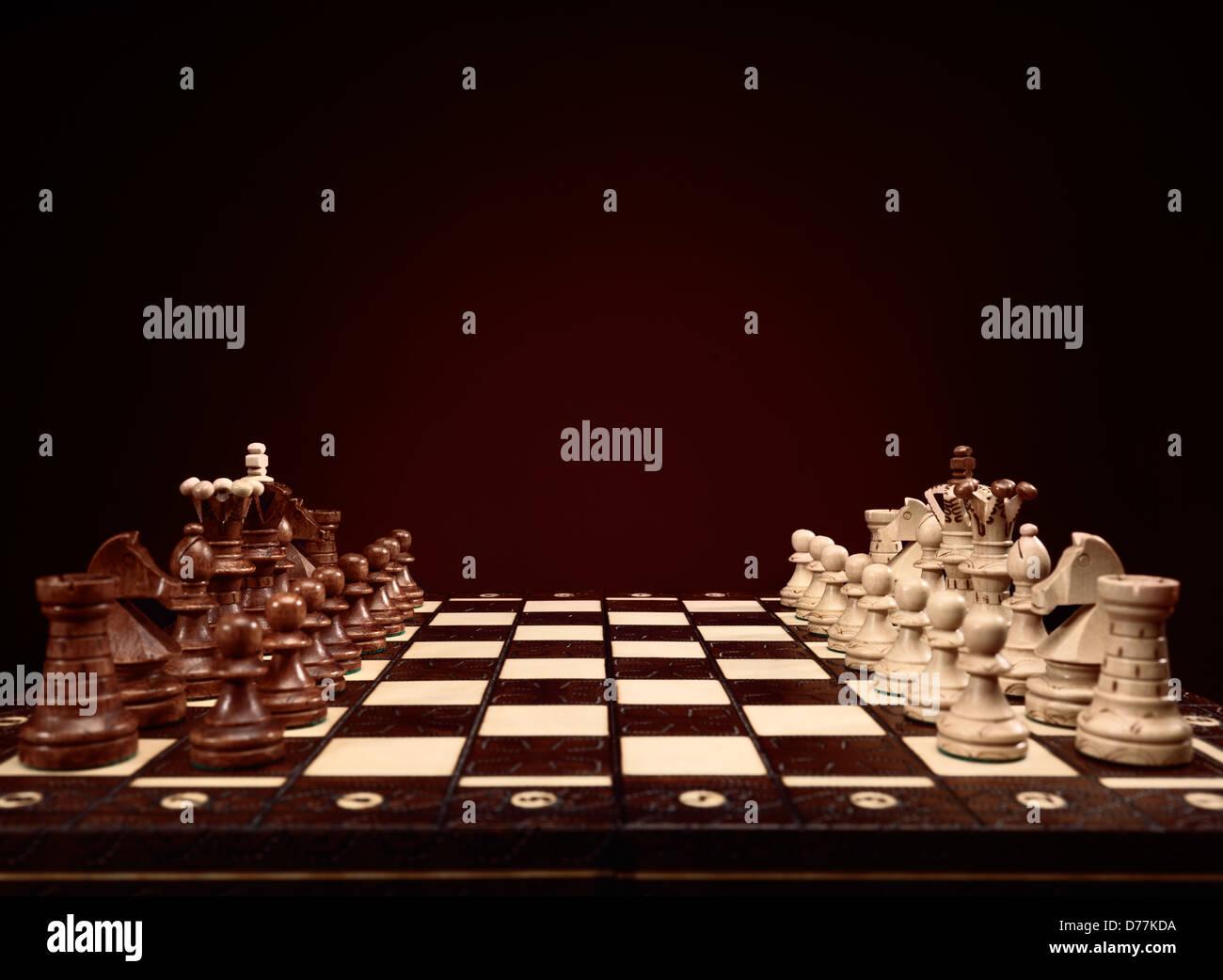 Scacchiera con pezzi di scacchi, gioco di bordo su sfondo marrone Immagini Stock