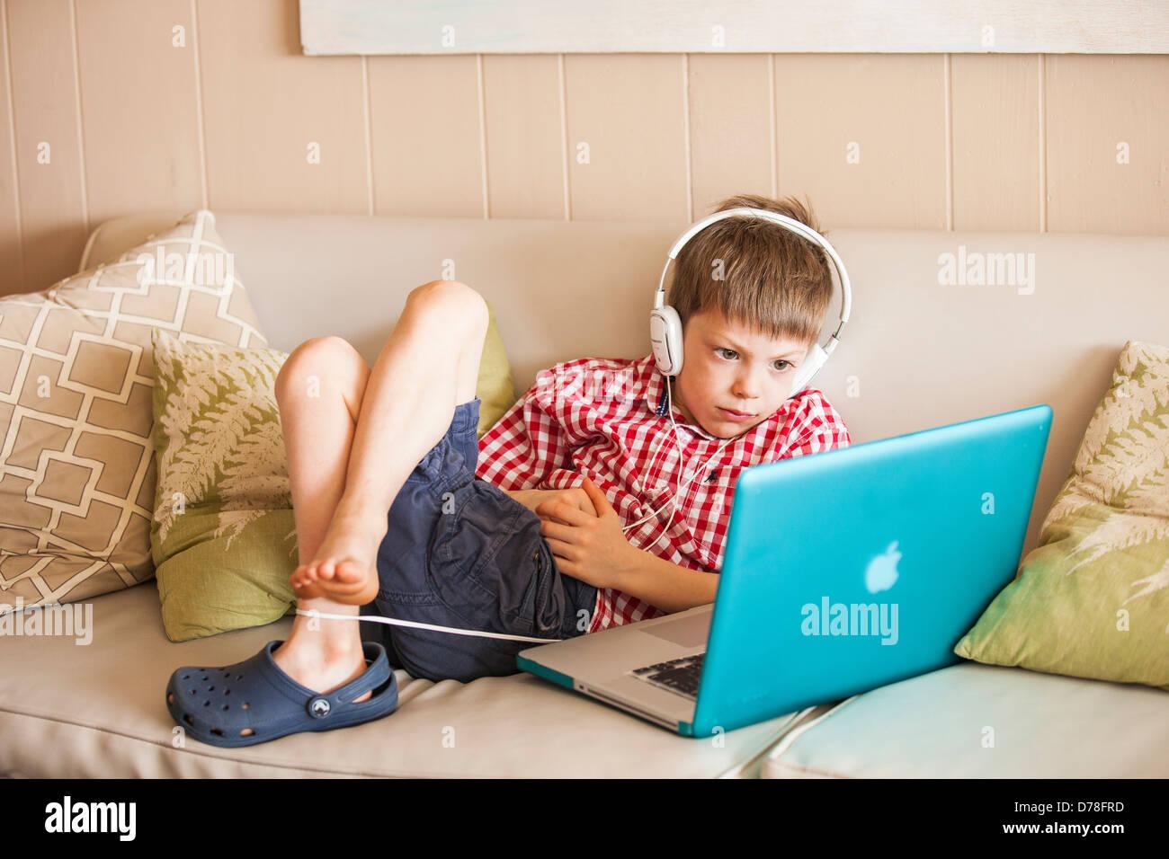 Boy utilizzando laptop e le cuffie Immagini Stock