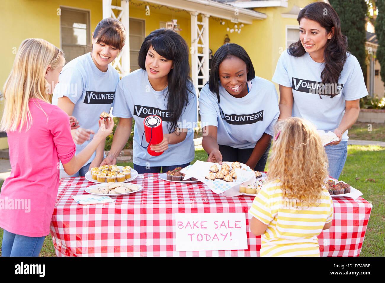 Le donne e i bambini in esecuzione la carità cuocere la vendita Immagini Stock