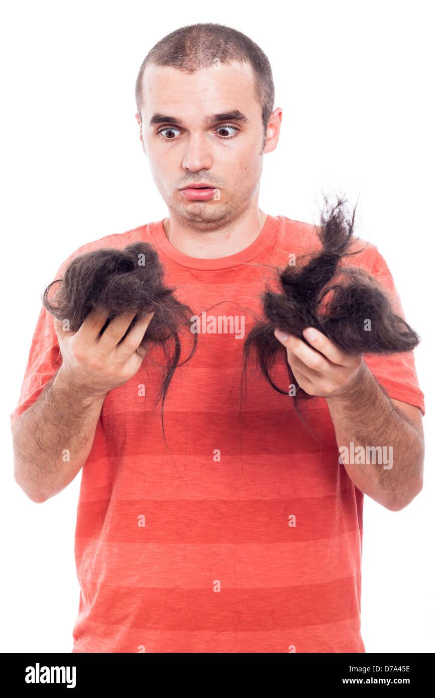 Scioccato uomo calvo tenendo i suoi lunghi capelli rasata, isolato su sfondo bianco Immagini Stock