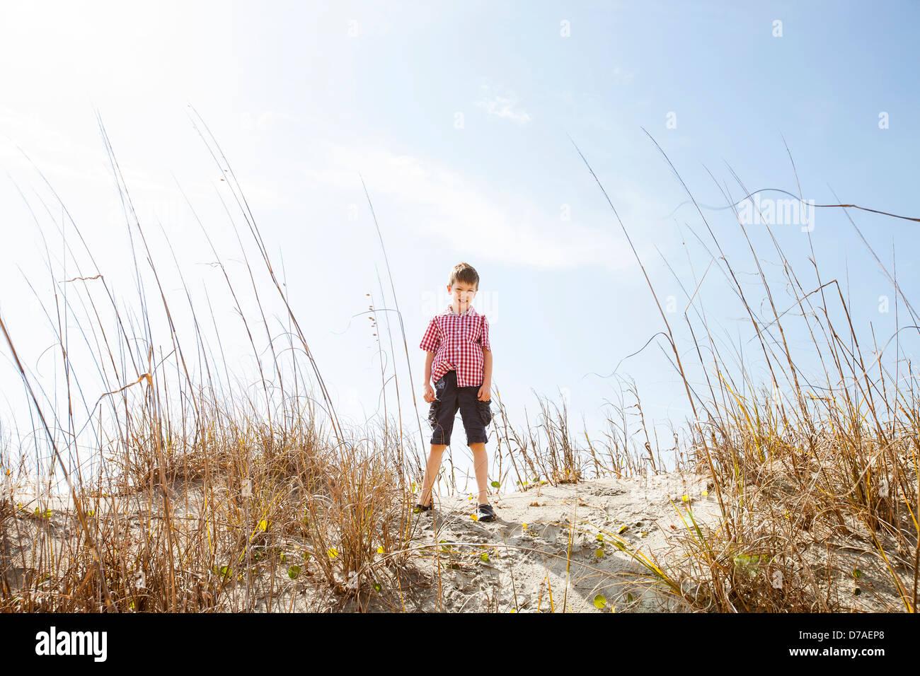 Bambino in piedi sulla sommità della duna di sabbia Immagini Stock