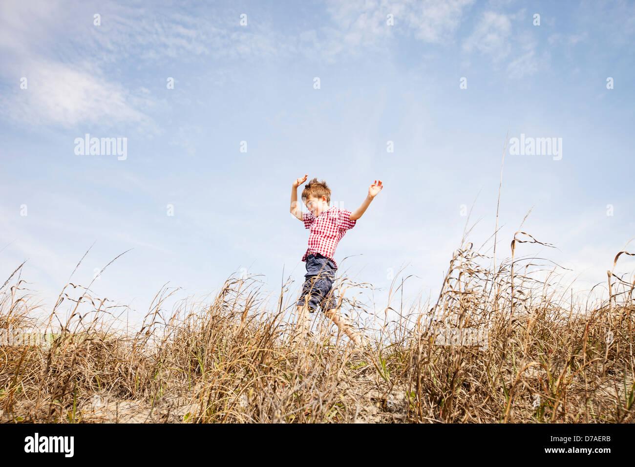 Bambino che corre attraverso le dune Immagini Stock