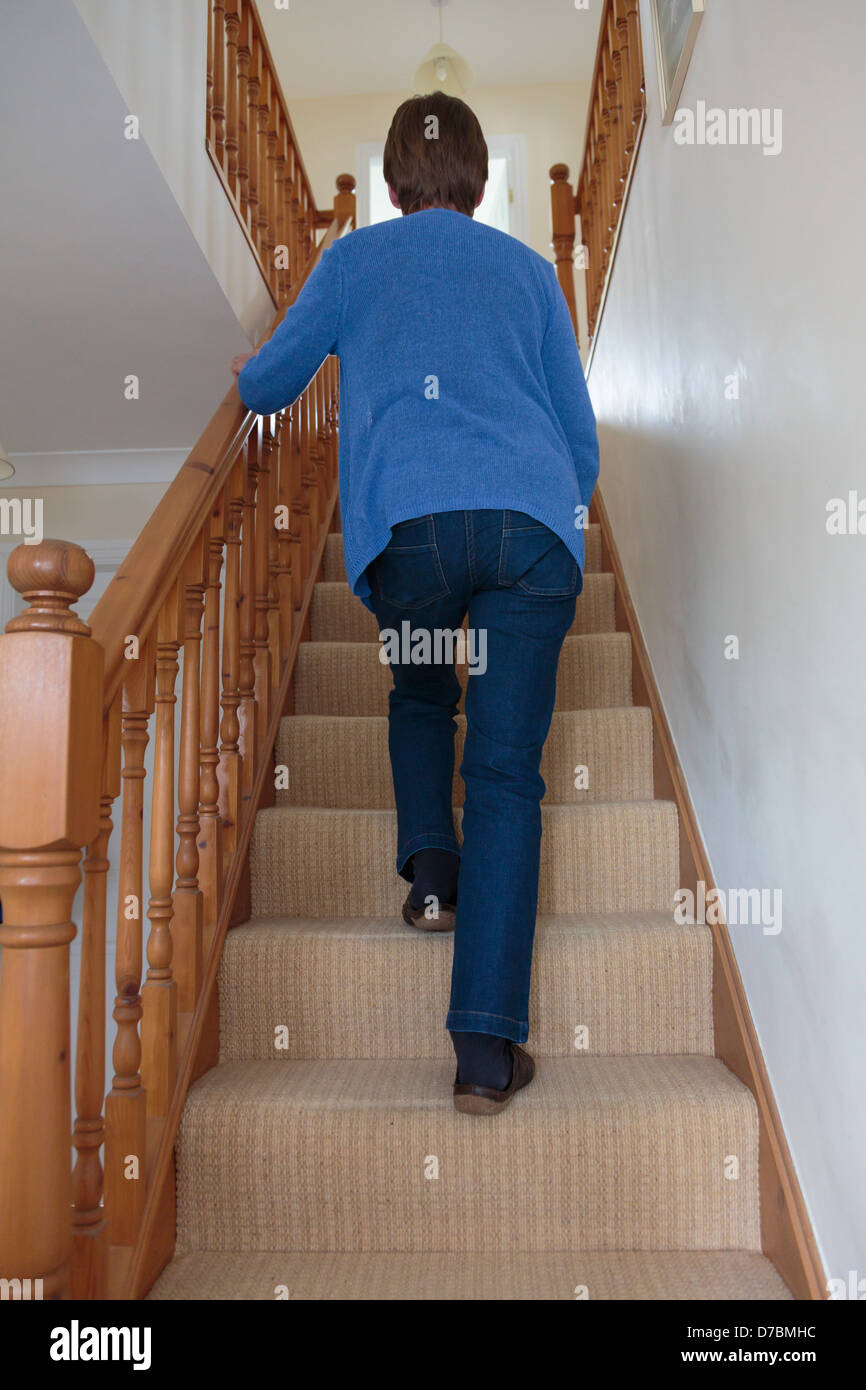 Scena quotidiana di una donna senior salendo le scale di tenere su una ringhiera in legno ferrovia a casa visto Immagini Stock