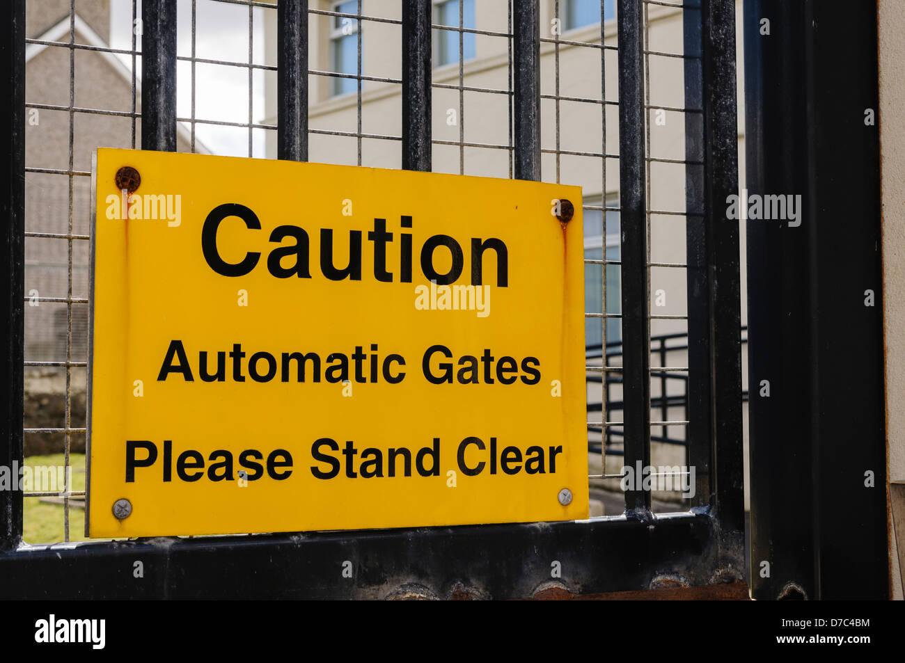 """Segno a una pesantemente PSNI fortificato stazione di polizia """"Attenzione: cancelli automatici. Si prega di Immagini Stock"""