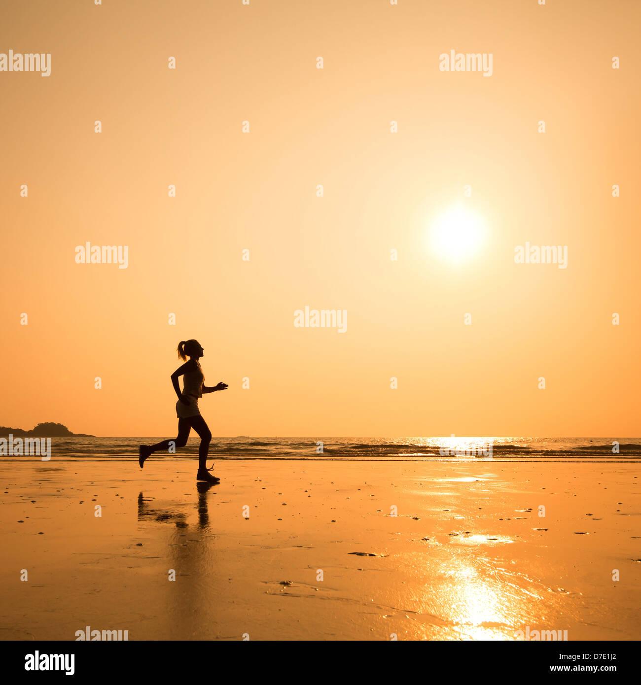 Eseguire la funzione, silhouette di donna sulla spiaggia Immagini Stock