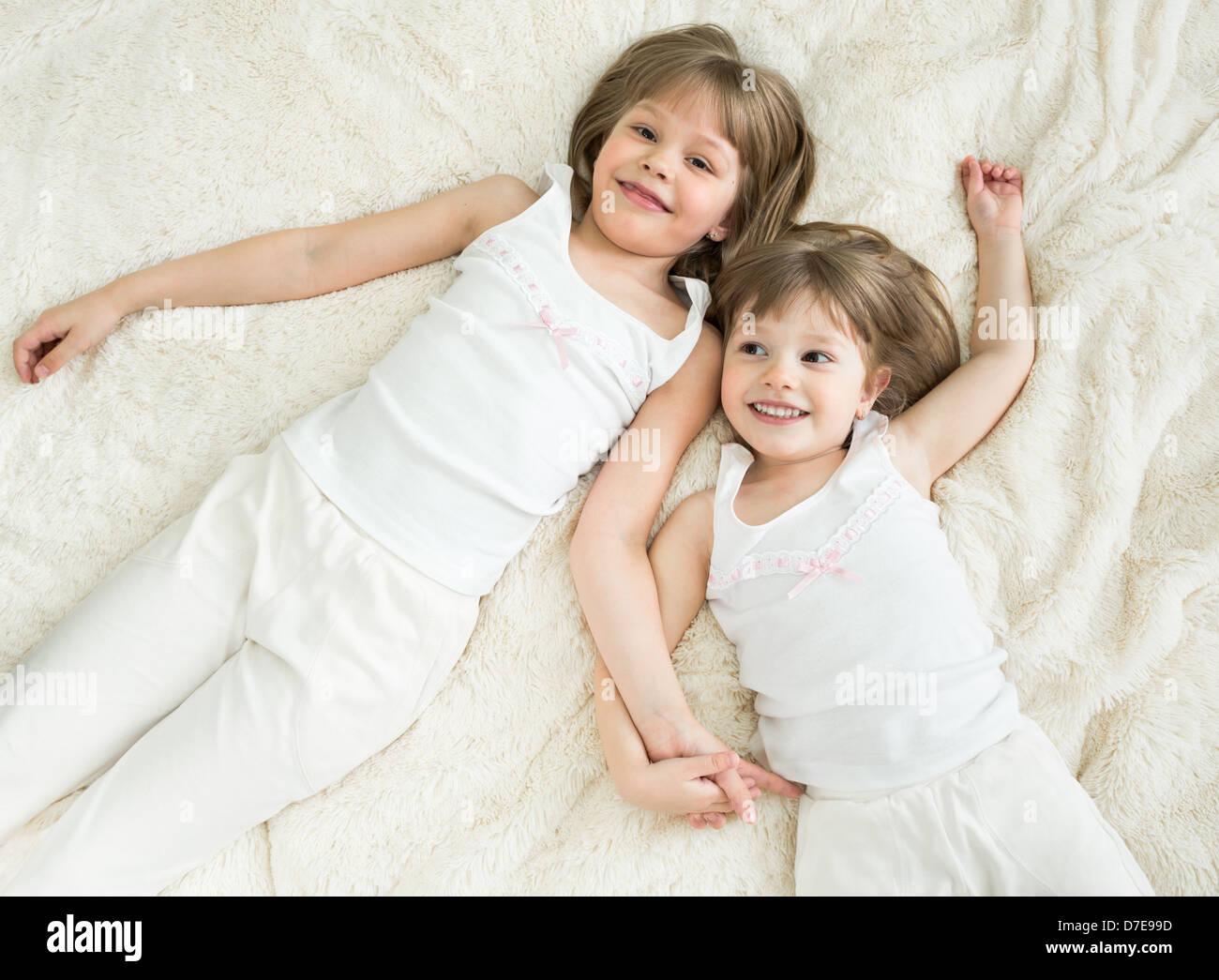 Felice piccole sorelle giacente sul retro vista superiore Immagini Stock