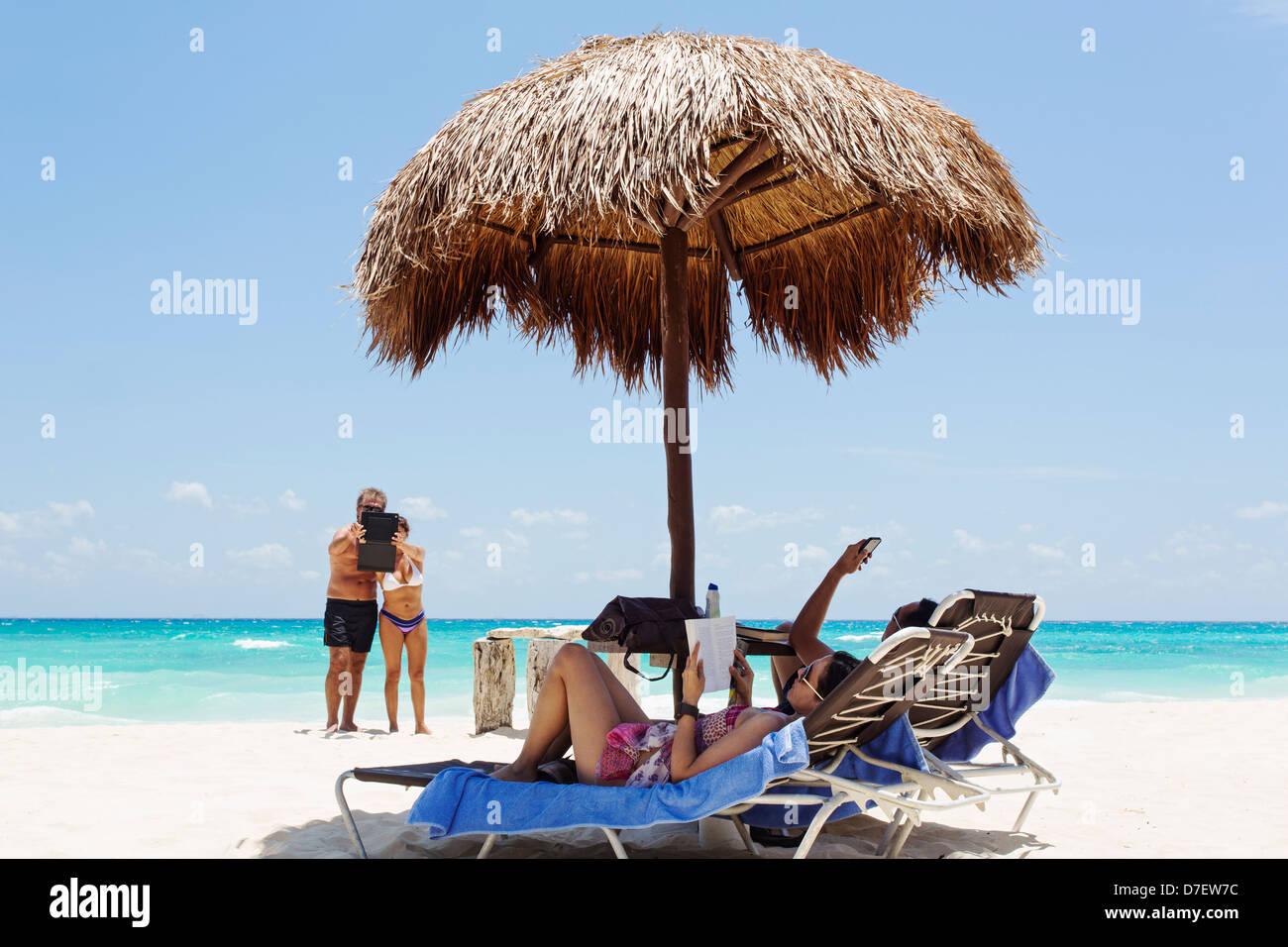 La gente sulla spiaggia utilizzando i-phone e i-pad Immagini Stock