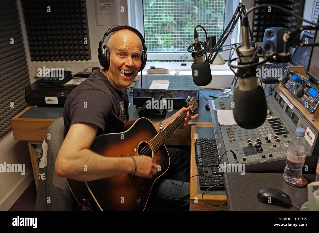 Una radio locale DJ suona la chitarra nel suo show alla fonte 96,1 FM che trasmette a Falmouth e le aree circostanti. Immagini Stock