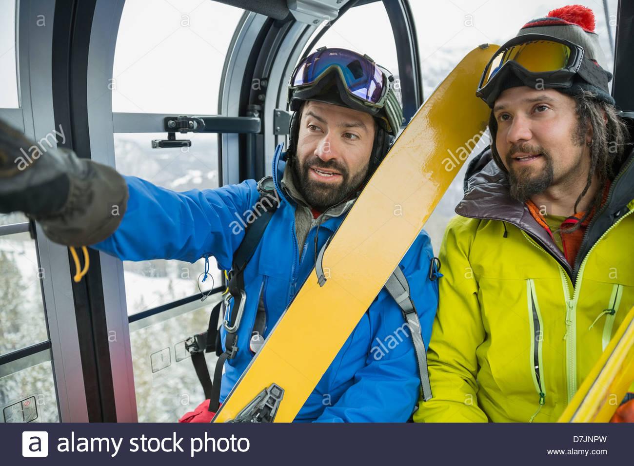 Gli sciatori maschio parlando in gondola in montagna Immagini Stock
