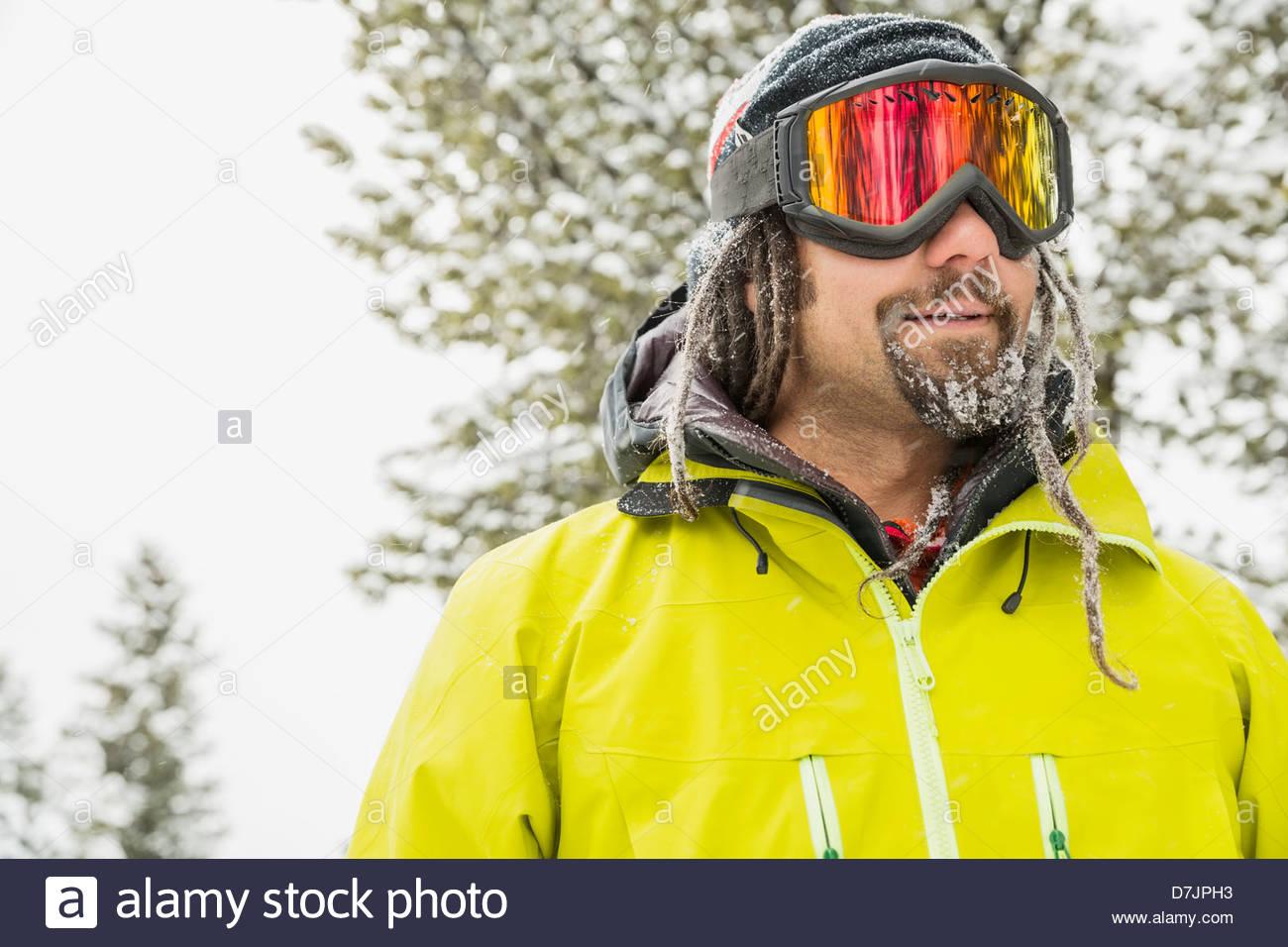 Uomo che indossa gli occhiali da sci in inverno Immagini Stock