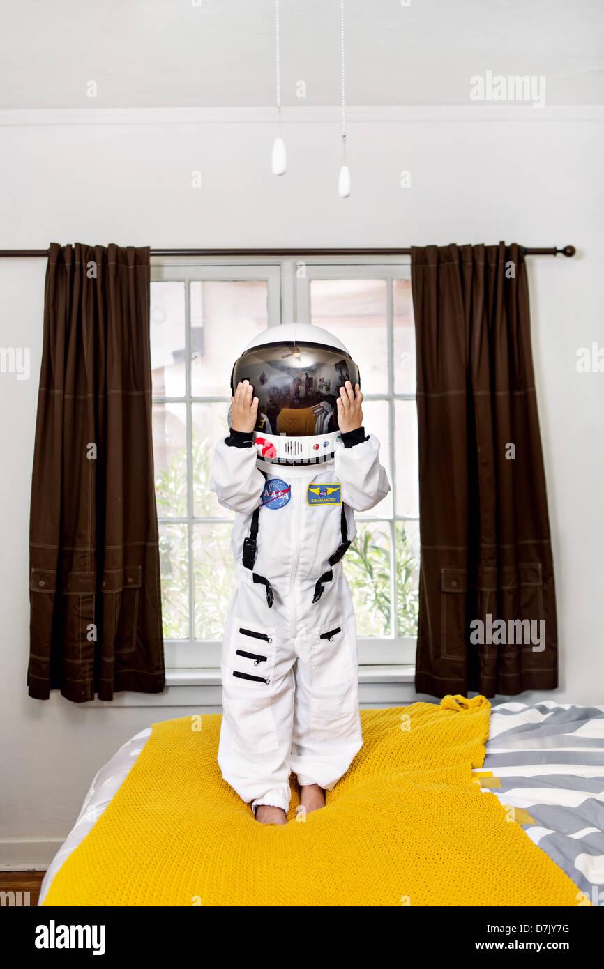Ritratto di ragazzo in piedi sul suo letto in tuta spaziale Immagini Stock