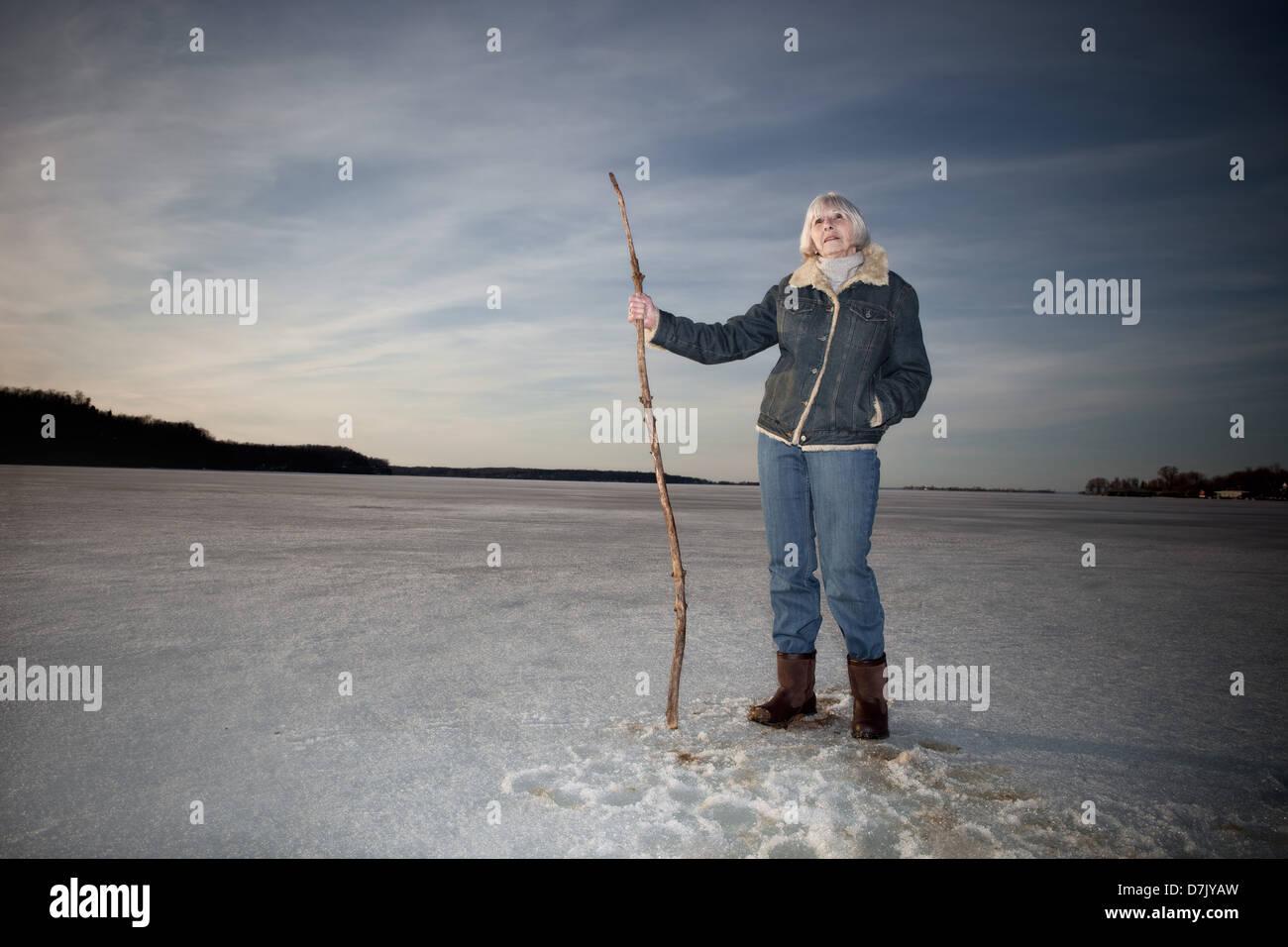 Ritratto ambientale della donna nella sua 70's in piedi sul lago di stecco di presa della canna da zucchero Immagini Stock